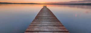 inheritance tax policies WMT photo of long wooden pier stretching far out into the lake as sunsets