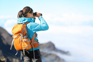 Hiker looking in binoculars enjoying spectacular view on mountain top above the clouds.