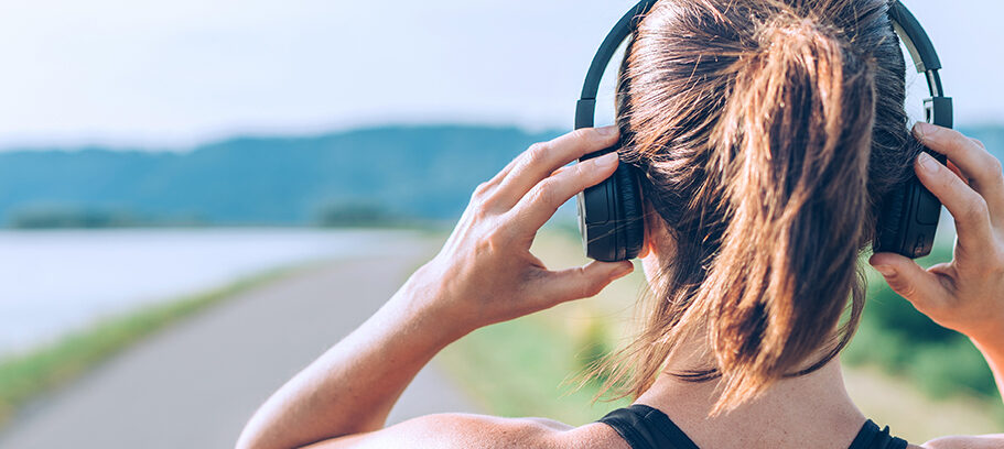 Young teenager girl adjusting wireless headphones before starting jogging and listening to music. Web page header cropping.